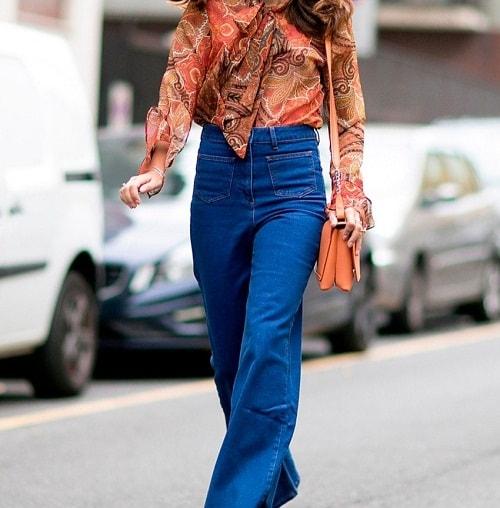 девушка в джинсах клеш и сумочкой